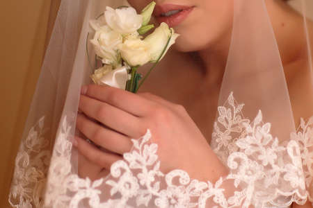 face covered: Bridal hands holding beautiful wedding boutonniere of white roses flowers near her face covered with elegant marriage veil Stock Photo