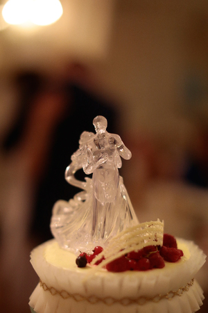 topper: Wedding cake with plastic transparent beautiful topper with dancing couple on blur background