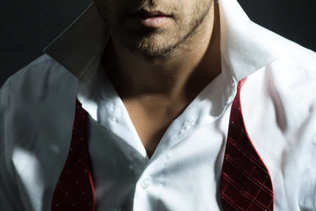 untied: Sexy man with unshaven face in white shirt and red untied bow closeup Stock Photo