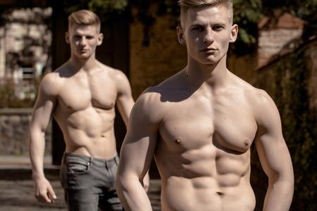 pechos: hermanos gemelos masculinos jóvenes culturistas musculares Macho con el torso desnudo corte de pelo estilo en pantalones vaqueros plantean al aire libre en el fondo borroso Foto de archivo