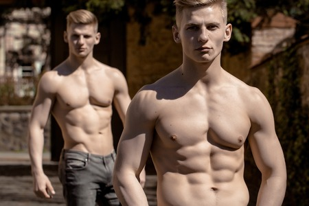 bare breasts: Young twin brothers male muscular bodybuilders macho with bare torso stylish haircut in jeans pose outdoor on blurred background