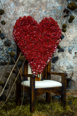 arranging chairs: Floral arrangement with red rose flowers in shape of heart on chair outdoor on stony wall background