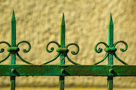 yellow wall: Old fence rusty forged metallized with peeled green paint on sunny day on yellow wall background