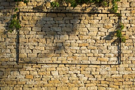 Stone wall of beige uneven cracked brick surface with metallized frame on mason background Stock Photo