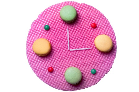 dragee: Sweet clock made of pink round waffle green and yellow macaron and small dragee candies with candles isolated on white background