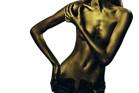 bodyart: Golden female body of young sexy beautiful woman with bare chest and belly isolated on white background. Metalic art, body art