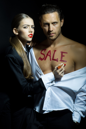 attractive macho: Attractive young couple of pretty girl with red lips and macho man in shirt with bare chest and sale text with lipstick on black background