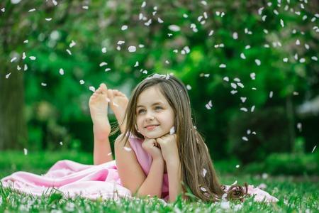 長いブルネットの髪と春花花びら屋外の緑の芝生の上、裸足が横になっている笑顔とピンクのドレスの美しい少女