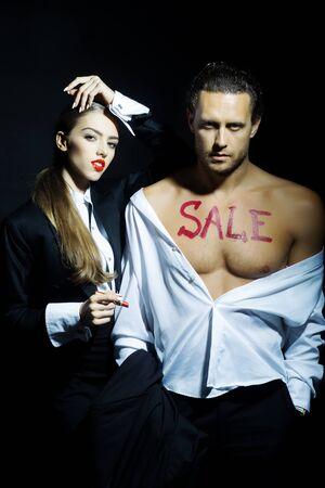 nackte brust: Attraktive junge Paar von h�bschen M�dchen mit den roten Lippen und Macho-Mann in T-Shirt mit nacktem Oberk�rper und den Verkauf Text mit Lippenstift auf schwarzem Hintergrund