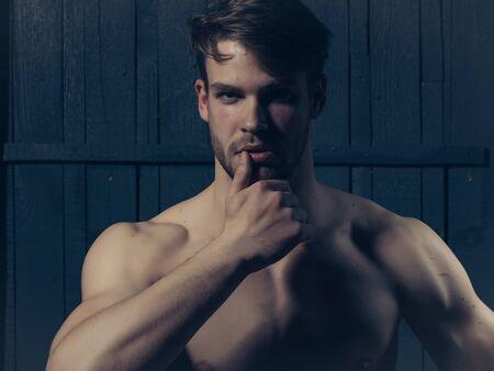 nackte brust: Junger Mann mit dem muskul�sen nackten Brust und sexy K�rper auf h�lzernen Hintergrund posiert im Studio