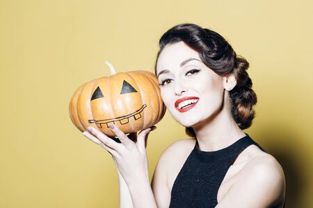 Smiling woman with beautiful face and retro hairdo and red lips holding pumpkin in studio on yellow background.