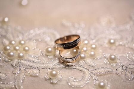 wedding bands: Wedding bands on white cloth richly embroidered with pearls on blurred background
