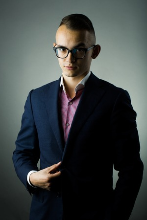 sociable: young fashion businessman with nerd glasses and stylish hairdo in jacket posing on grey background