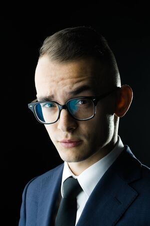 sociable: young fashion businessman with nerd glasses and stylish hairdo in jacket with tie on studio background closeup