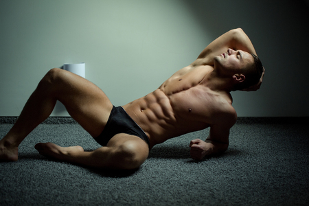 body male: Young man with beautiful muscular torso in underwear lying on floor