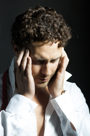 untied: Handsome sexy man with curly hair and unshaven face in white shirt and red untied bow holding hands near head in headache on black background