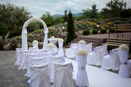 Rows of white chairs and wedding arch for marriage ceremony decorated with flowers and lilac bows & Rows Of White Chairs And Wedding Arch For Marriage Ceremony ...