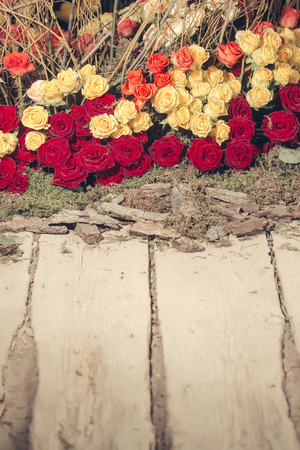 nosegay: Floral arrangement with colorful rose flowers and wooden twigs on wood floor, copy space Stock Photo