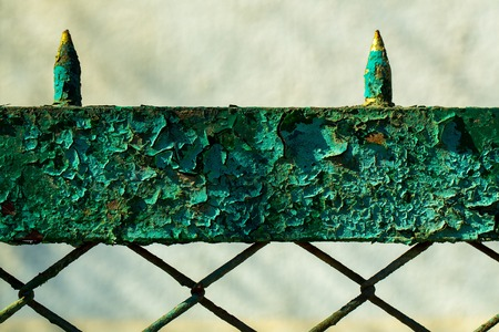 metallized: Old fence rusty forged metallized with peeled green paint on sunny day on grey background Stock Photo