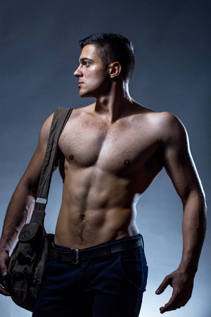 body bag: Young handsome man with muscular body bare torso posing in studio with training bag on chest on grey background