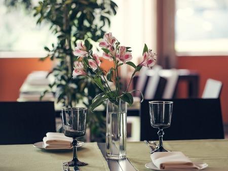 alstromeria: Pink alstromeria with green leaves in vase on table near empty glasses in cafe interior Stock Photo