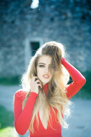 sexi: Young woman with long hair and pretty face in sexy red dress outdoor sunny day closeup