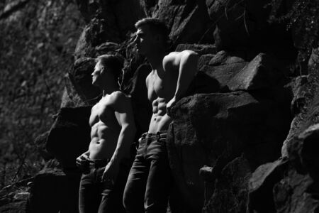 Strong torso of twin men shirtless in jeans with muscular body pose outside black and white on mountain background
