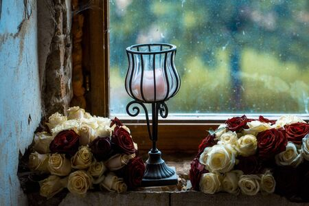 bunches: Old dirty window with two flower bunches and candlestick on grunge cement windowsill on blurred glass background Stock Photo