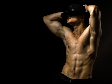 nackte brust: Young handsome man with muscular body in hat with bare chest and torso posing in studio on black background, copy space