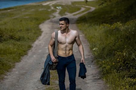 nackte brust: Junger stattlicher Mann mit muskulösen Körper und Rumpf auf dem Boden Straße mit Trainingstasche auf nackte Brust im Freien in der Nähe von grünem Gras gehen