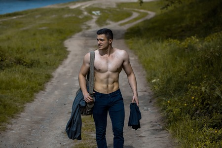 nackte brust: Young handsome man with muscular body and torso going on ground road near green grass with training bag on bare chest outdoor