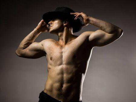 nackte brust: Junger stattlicher Mann mit muskulösen Körper in Hut mit nackten Brust und Rumpf im Studio posiert auf grauem Hintergrund Lizenzfreie Bilder