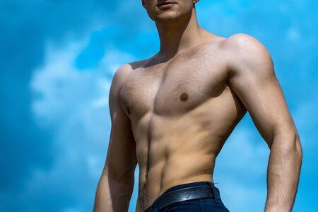 nackte brust: Junger stattlicher Mann mit muskul�sen K�rper nackte Brust und Rumpf auf bew�lkten blauen Himmel Hintergrund posiert im Freien