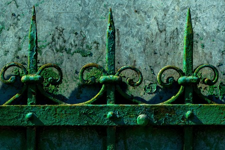 metallized: Old fence rusty forged metallized with peeled green paint on sunny day on grey wall background