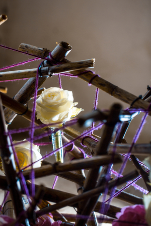 tangled: Bamboo sticks tangled with violet knitting wool and fresh roses on grey background