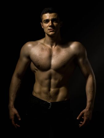 bare chest: Young handsome man with muscular body with bare chest and torso posing in studio on black background