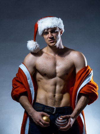 nackte brust: Young handsome man with muscular body bare chest and torso in santa claus coat and hat posing in studio on grey background