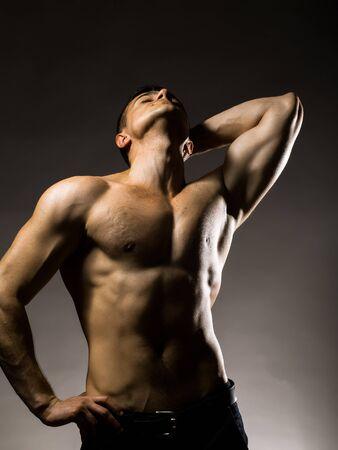 nackte brust: Junger stattlicher Mann mit muskul�sen K�rper mit nackten Brust und Rumpf auf grauem Hintergrund im Studio aufwirft Lizenzfreie Bilder