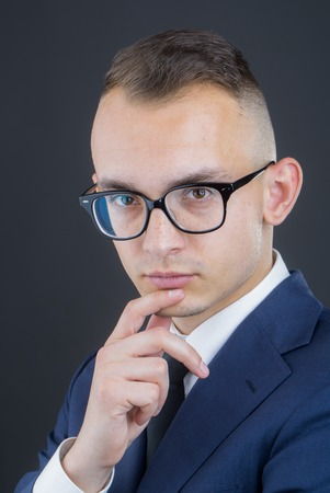 sociable: young fashion businessman with nerd glasses on thoughtful face and stylish hairdo in jacket with tie on studio background Stock Photo