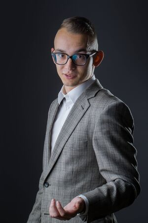 sociable: young fashion businessman talking with nerd glasses on emotional face and stylish hairdo in jacket on studio background