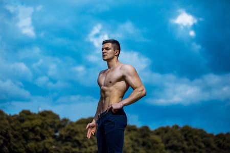 nackte brust: Junger stattlicher Mann mit muskulösen Körper nackte Brust und Rumpf in Hosen posiert im Freien an bewölkten blauen Himmel im Hintergrund