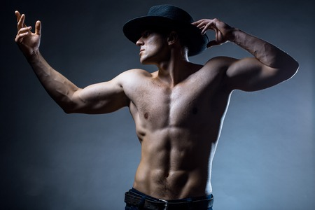 nackte brust: Junger stattlicher Mann mit muskul�sen K�rper in Hut mit nackten Brust und Rumpf im Studio posiert auf grauem Hintergrund Lizenzfreie Bilder