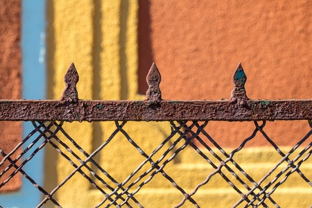 metallized: Old fence rusty forged metallized on sunny day on blurred plastered wall background