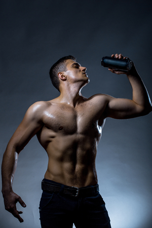 nackte brust: Young handsome man with muscular wet body bare chest and torso posing in studio holding black tin jar on grey background