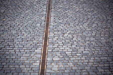 empedrado: carretera pavimentada con cubierta de agua de drenaje en el fondo de adoquines grises Foto de archivo