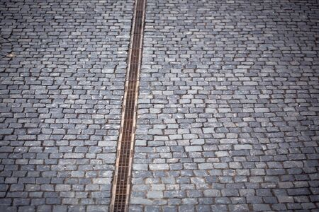 empedrado: Paved road with drain water cover on grey cobblestone background Foto de archivo