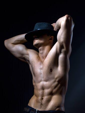 nackte brust: Junger stattlicher Mann mit muskul�sen K�rper in Hut mit nackten Brust und Rumpf im Studio auf schwarzem Hintergrund aufwirft
