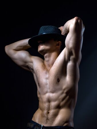 torso: Young handsome man with muscular body in hat with bare chest and torso posing in studio on black background