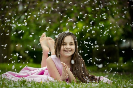 lying on grass: Beautiful little girl in pink dress with long brunette hair and smiling face lying barefoot on green grass in spring flower blossom petals outdoor