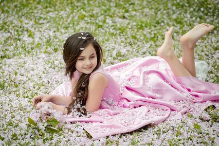 ragazze a piedi nudi: Bella bambina in abito rosa con i capelli lunghi bruna e sorridente volto felice che si trova a piedi nudi sul prato verde coperto di petali di fiori di primavera fiore esterno